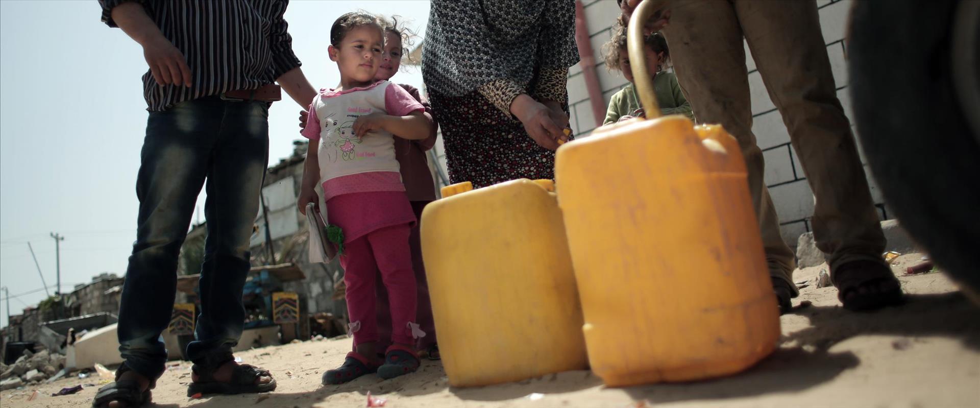 פלסטינים בעזה ממלאים בקבוקי מים