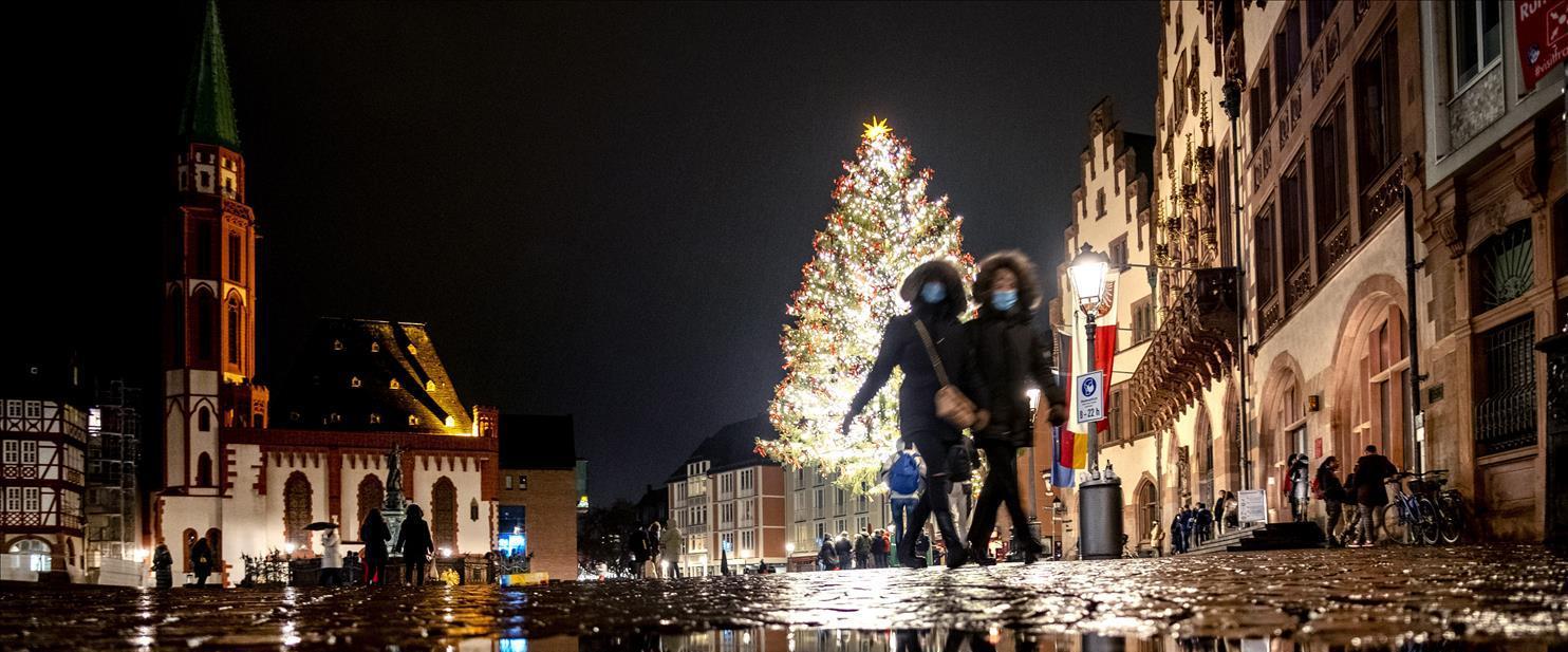 שניים הולכים עם מסכות בפרנקפורט, וברקע קישוטי חג ה