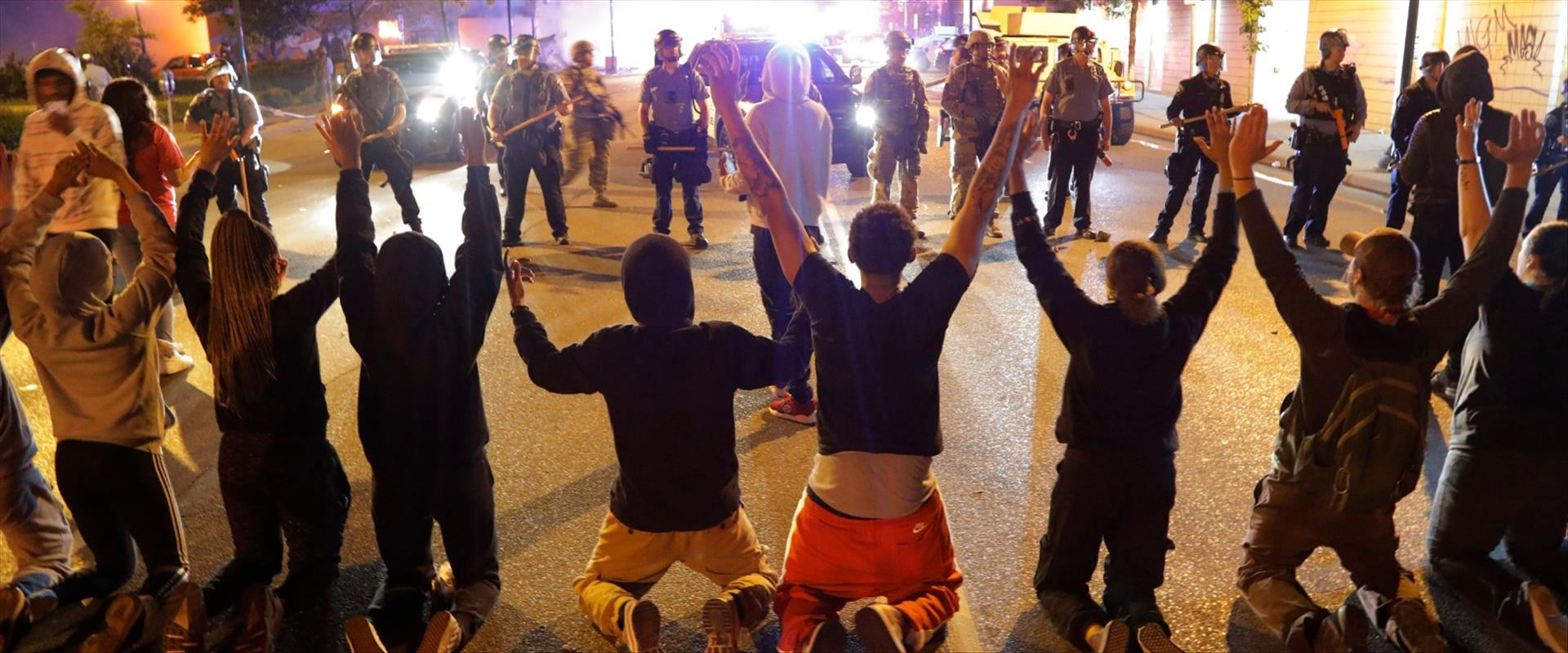 מפגינים כורעים ברך בפני שוטרים במיניאפוליס