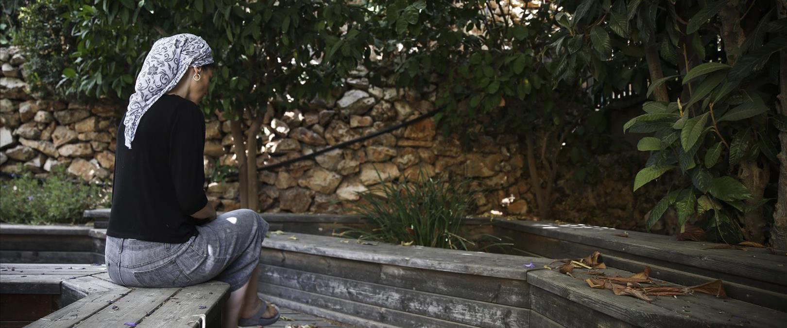 אישה דתייה עם שביס יושבת על ספסל