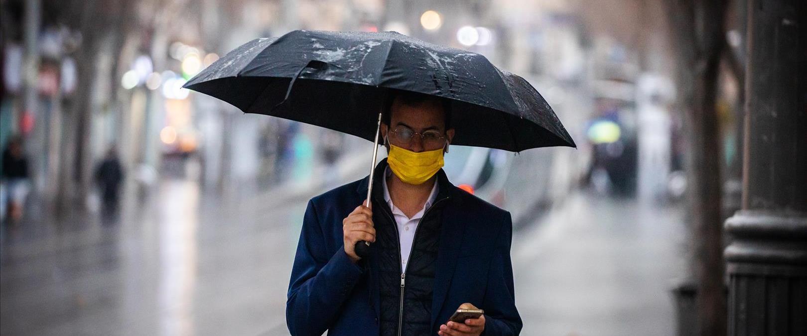איש צועד בגשם עם מטריה