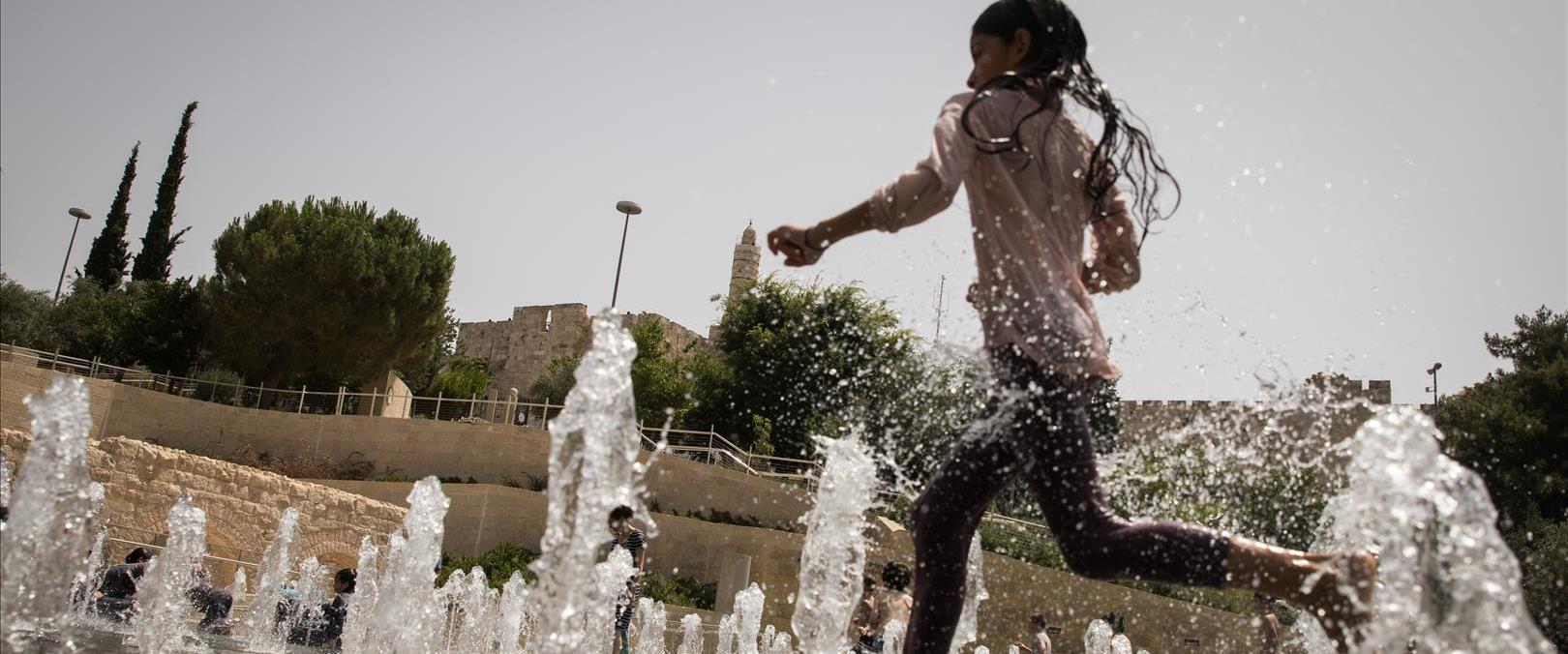 ילדה רצה במזרקה בשרב בירושלים, 2019