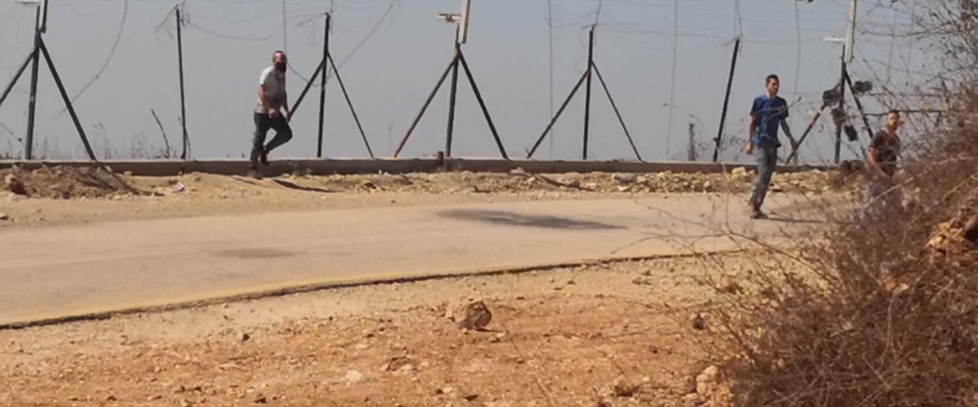 פלסטינים עוברים דרך פרצה בגדר הביטחון