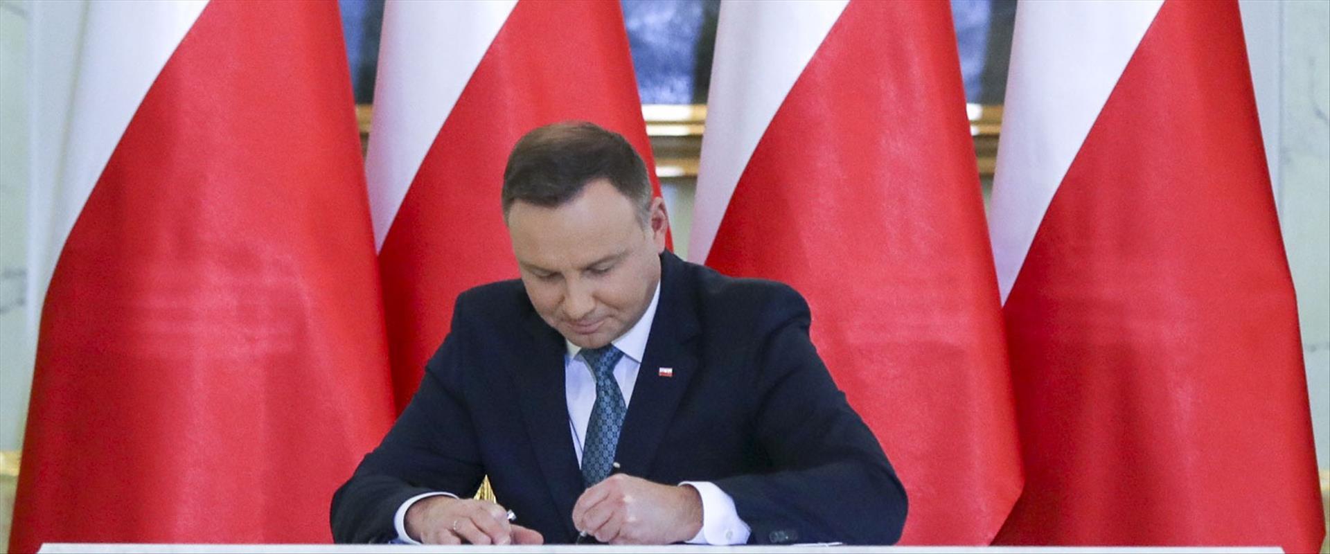 נשיא פולין אנדז'יי דודה חותם על חוק הרכוש