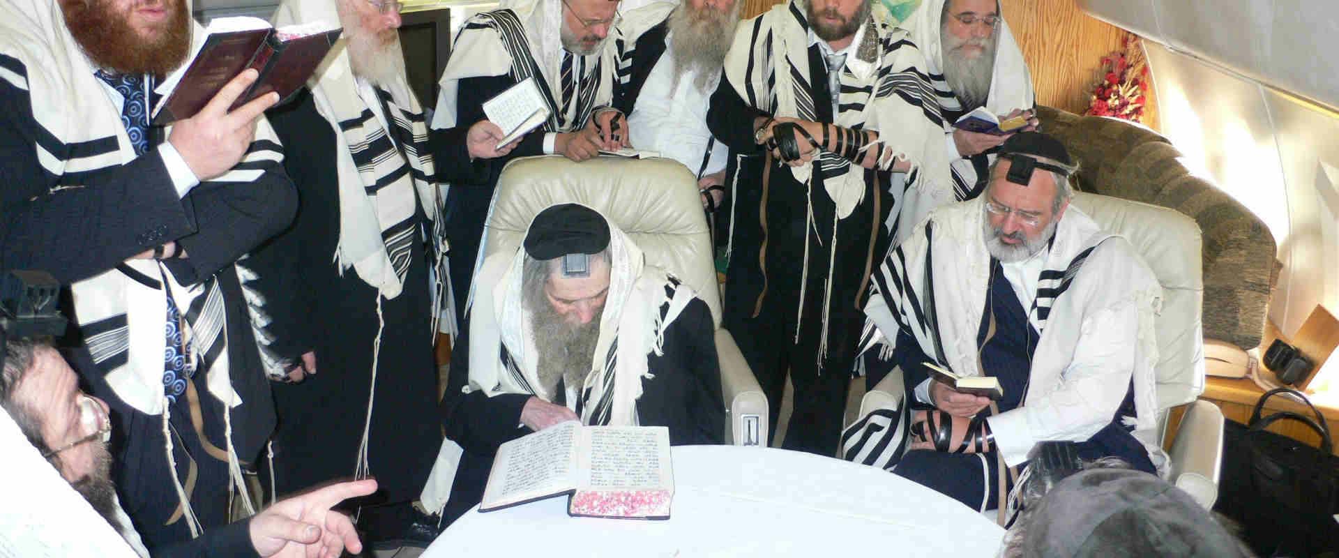 שמעון גליק יושב לצד הרב שטיינמן בתפילה במטוסו הפרט