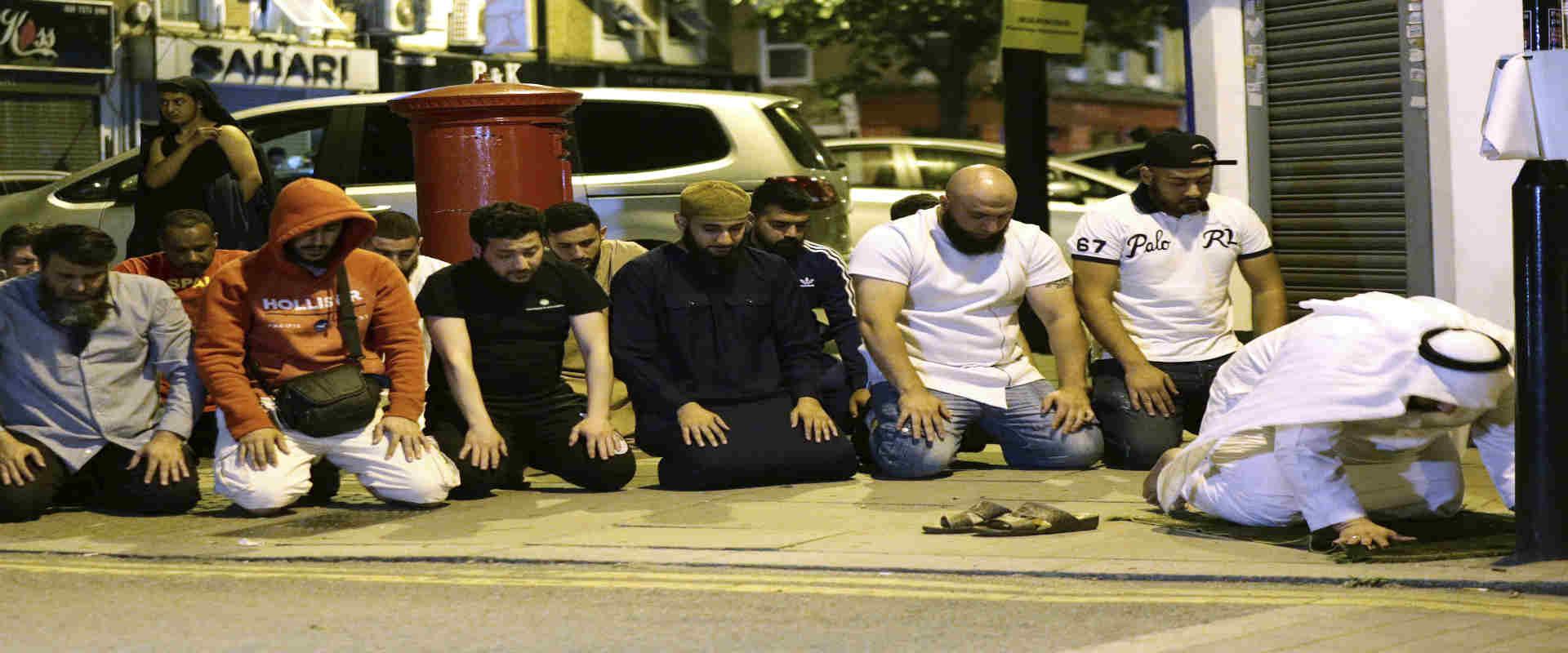 מוסלמים מתפללים ליד המסגד לאחר הפיגוע