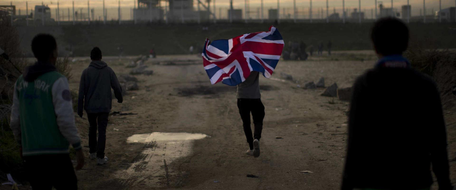 מבקש מקלט מניף דגל בריטניה במחנה פליטים בקאלה, צרפ