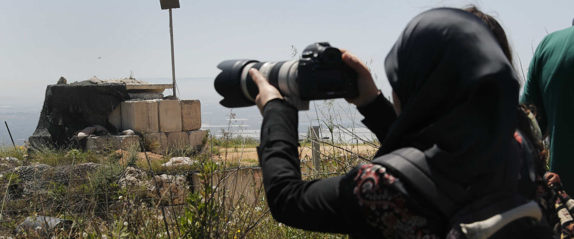 """אשה בלבנון מצלמת עמדת צה""""ל ליד הגבול, באפריל"""