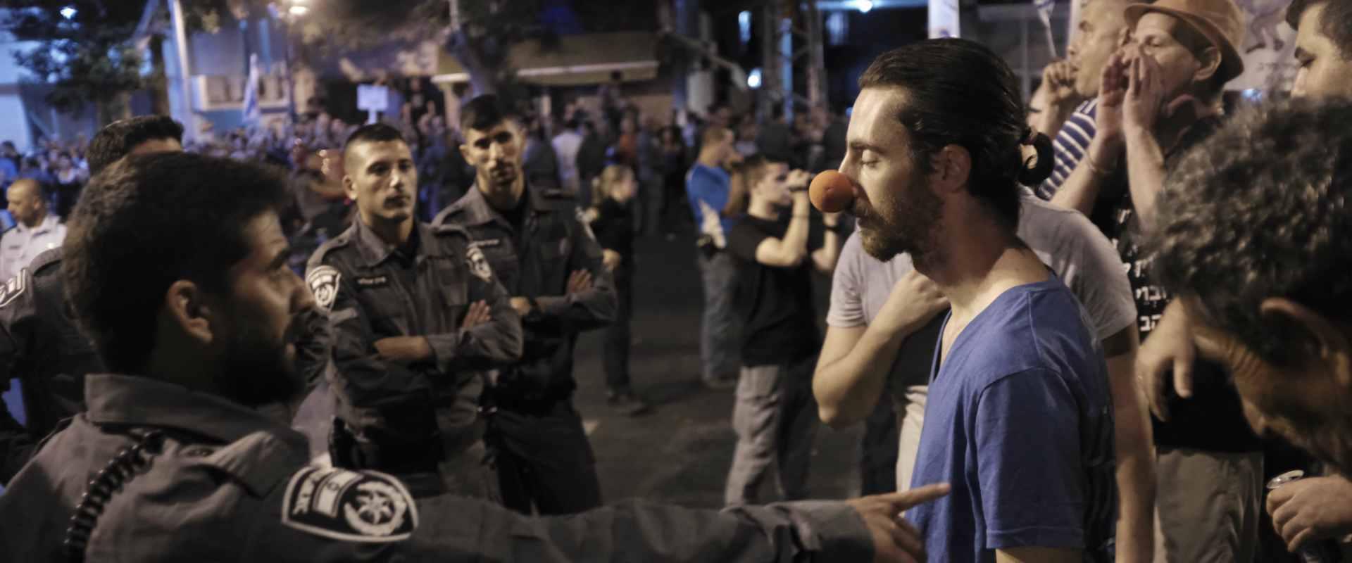 מפגין מול שוטרים בהפגנה בפתח תקווה