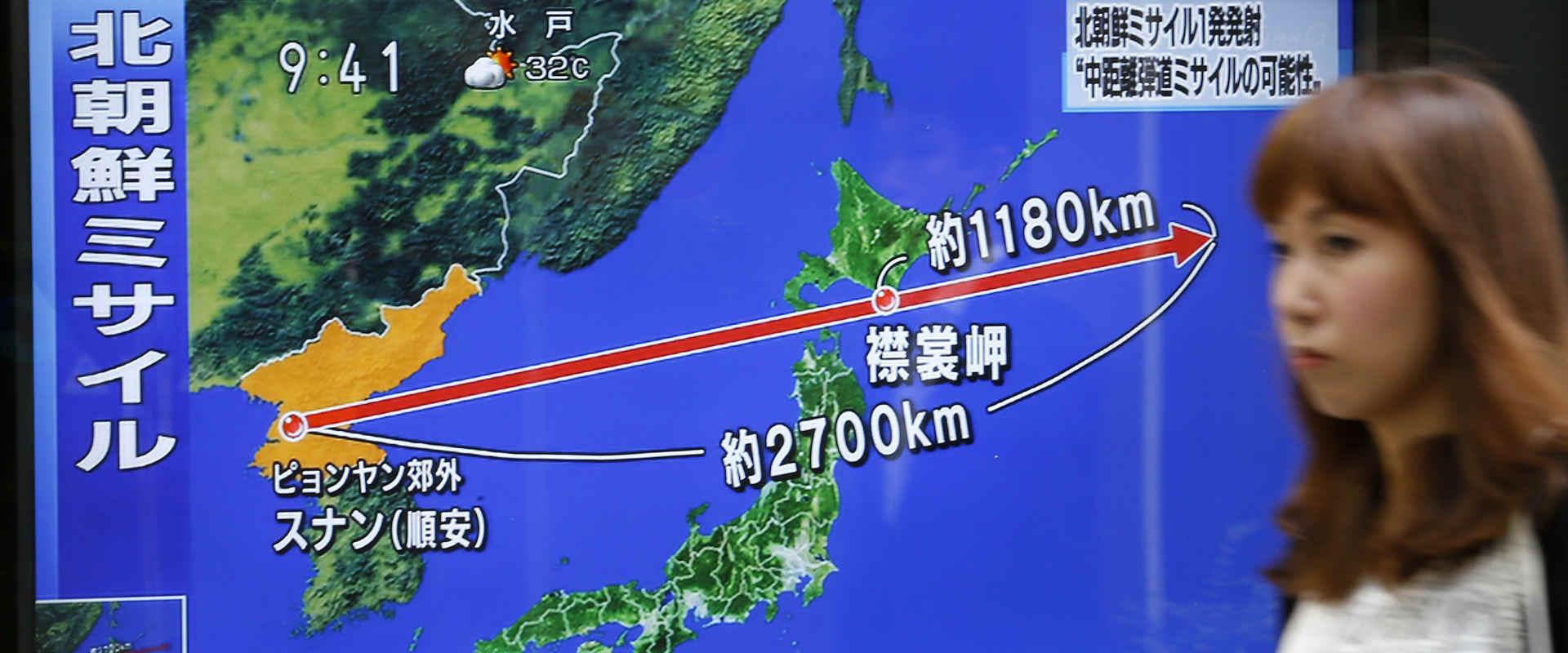 תושבת טוקיו ליד טלוויזיה המדווחת על שיגור הטיל