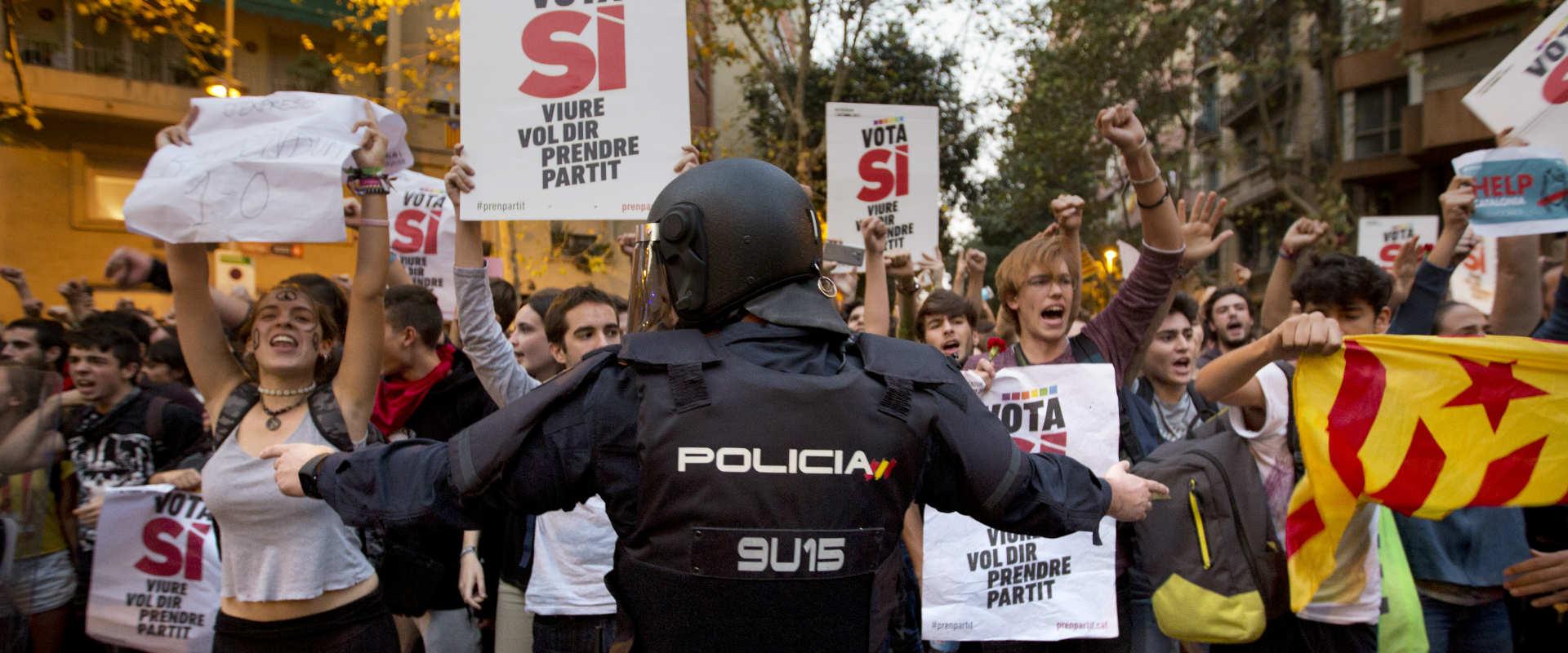 שוטר ספרדי עומד מול מפגינים קטלונים במהלך משאל העם