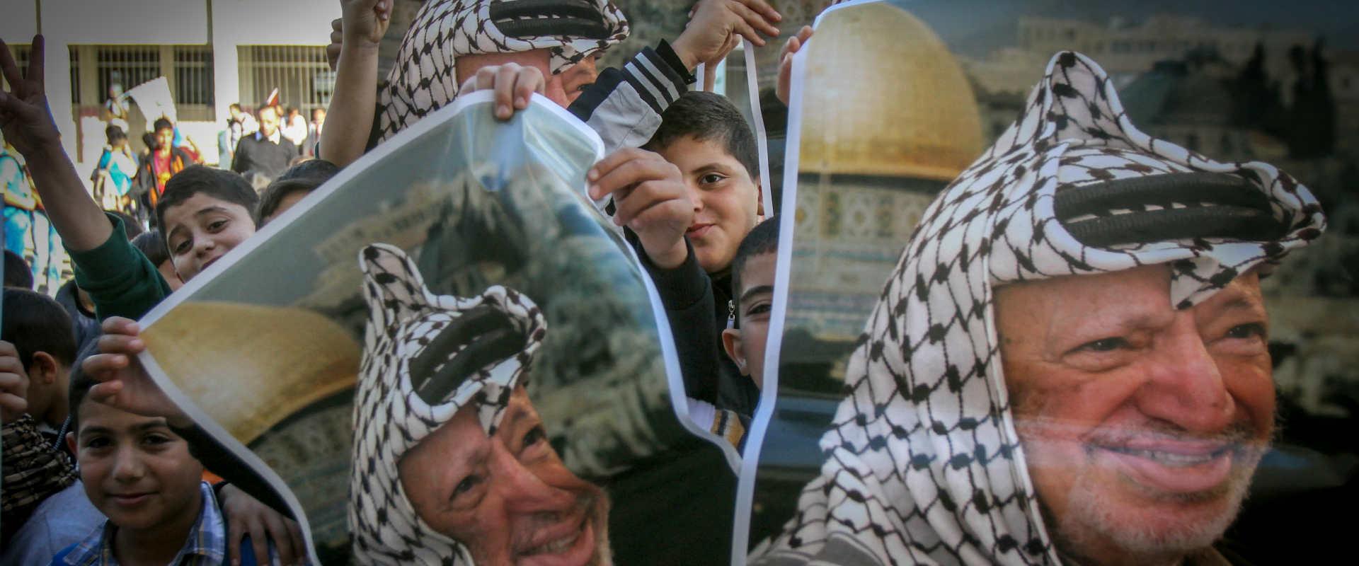ילדים פלסטינים מחזיקים כרזות עם דמותו של ערפאת