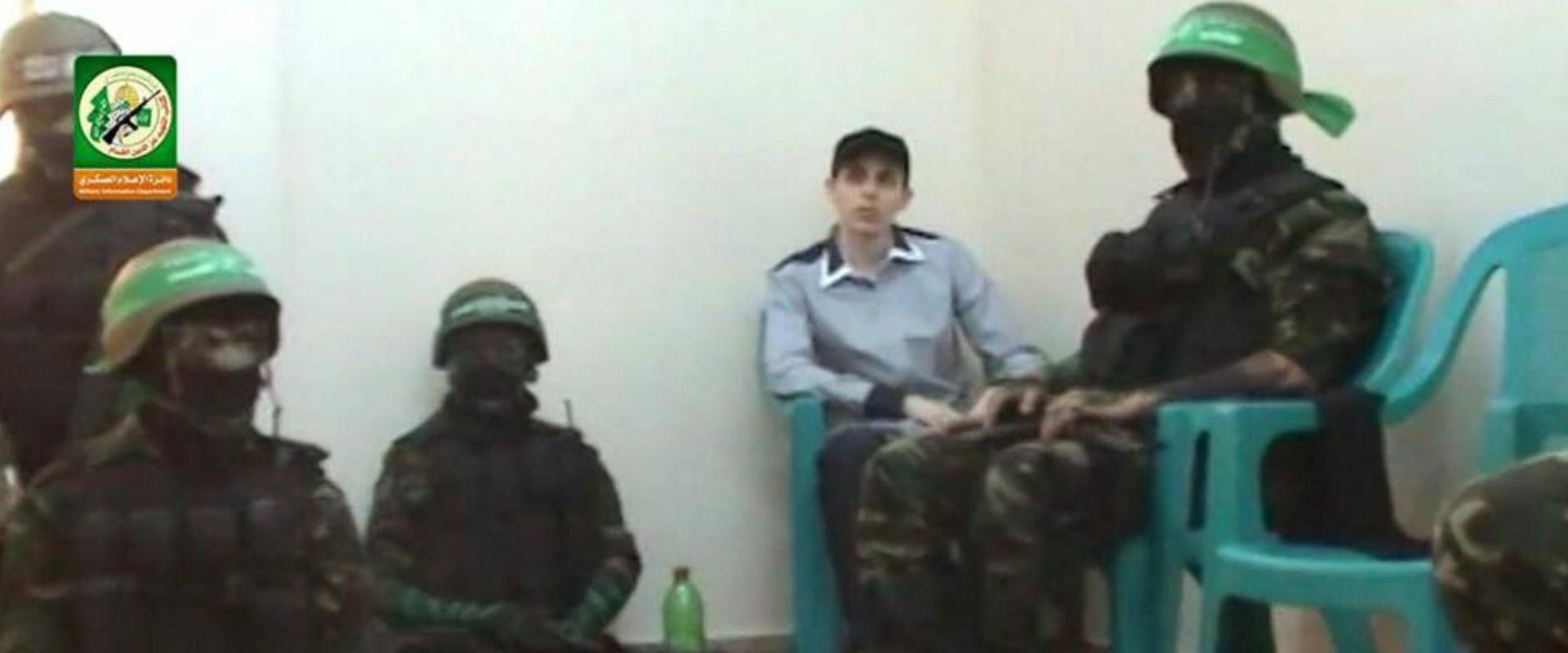 גלעד שליט יושב סביב מחבלי חמאס